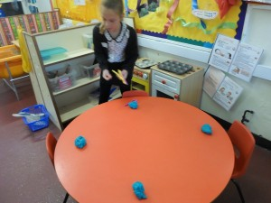 Putting scissors in the play dough to develop fine motor control